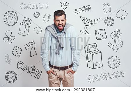 Bad Luck. Angry Young Man Keeping Hands In His Pockets And Shouting While Standing Against Grey Back