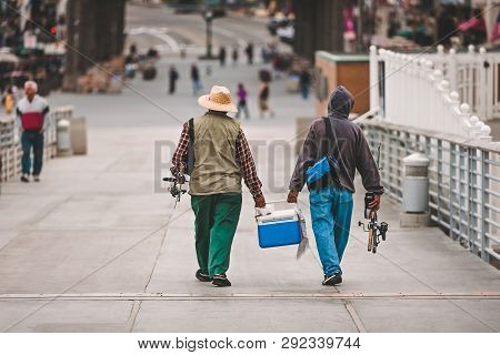 Two Men Dressed For Fishing And With Their Fishing Poles, Walk With A Blue Cooler Filled With Fish A