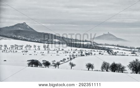 Two Hills With Castle Ruins In The Winter Landscape With Fields And Trees