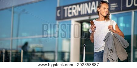 Young woman with her luggage at an international airport, after safe landing, arrival in her destination, leaving the airport, looking for a taxi