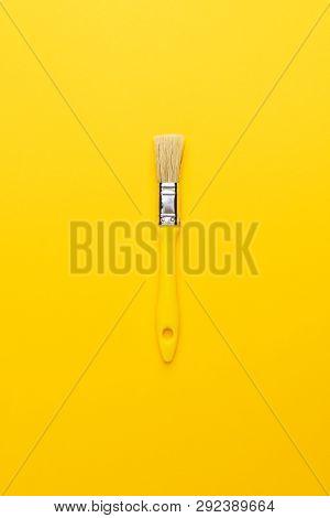 Paint Brush With Yellow Handle. Minimalist Shot Of Yellow Paint Brush. Top View Of The Paint Brush O