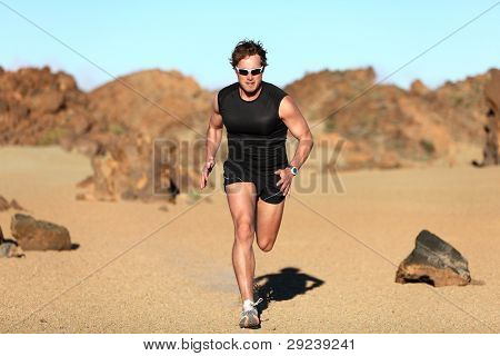 Runner running. Man sprinting in desert training for marathon. Young fit male fitness sport model working out outdoors in amazing desert landscape
