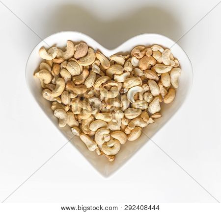 Nuts Arranged In Heart  On Background. Healthy Food Image Close Up Cashew Nuts. Love Texture On Whit