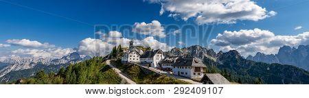 Village Of Monte Santo Di Lussari (1790 M) And The Peak Of Mangart (2677 M.) In The Julian Alps. Tar