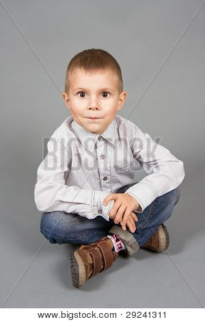 The boy sits on a grey background