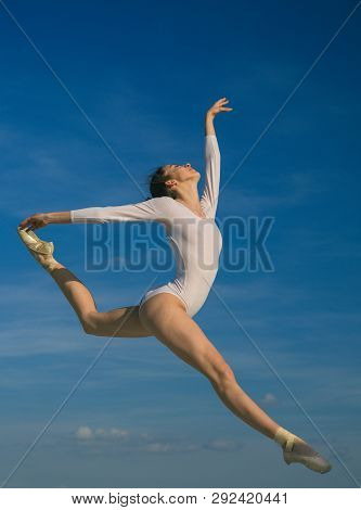 Graceful Beauty. Concert Performance Dance. Young Ballerina Jumping On Blue Sky. Classic Dance Style