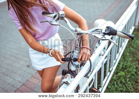 Close-up, A Girl In Summer In City, Puts Lock On Her Bike, Protection Against Theft, Bicycle Parking