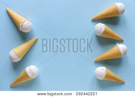 Side Border Of Frozen Ice Cream Cones With Scoops Of Creamy Vanilla Dessert On A Cool Toned Blue Bac