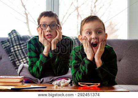 Surprised Kids On The Couch Watching Tv. The Children Opened Their Mouths In Shock