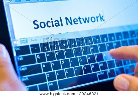 social network on tablet-pc with finger on virtual keyboard