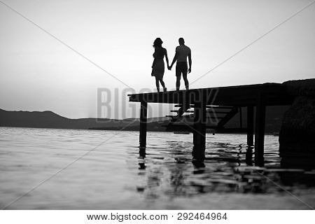 Dusk Couple Silhouette On Pier At Sea Water. Dusk Couple Silhouette Walk At Sunset Sea Resort