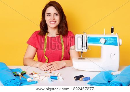 Horisontal Portrait Of Young Pretty Woman In Casual Red T Shirt With Sewing Machine And Measuring Ta