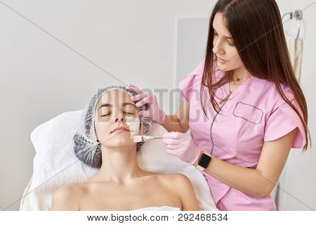 poster of Cosmetologist applys peeling mask to her client face. Woman getting facial care by beautician at spa salon, has cleansing procedure. Spa, beauty treatment, skincare, cosmetology salon concept.