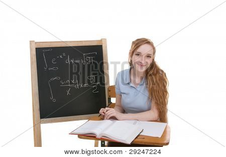High school or college Caucasian redhead woman student sitting by the desk. Blank blackboard with advanced mathematical formulas is visible in background