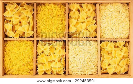 Wooden Box Storing A Variety Of Pasta. Farfalle, Noodles And Orzo Pasta.