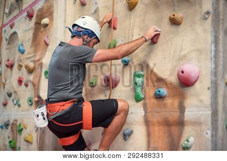 Young Man Practicing Rock Climbing On Artificial Wall Indoors.