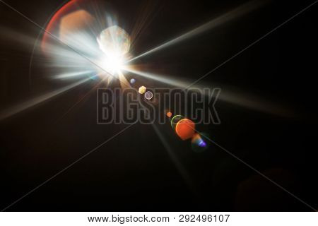 Lens Flare. Light over black background. Easy to add overlay or screen filter over photos. Abstract sun burst with digital lens flare background. Gleams rounded and hexagonal shapes, rainbow halo. poster