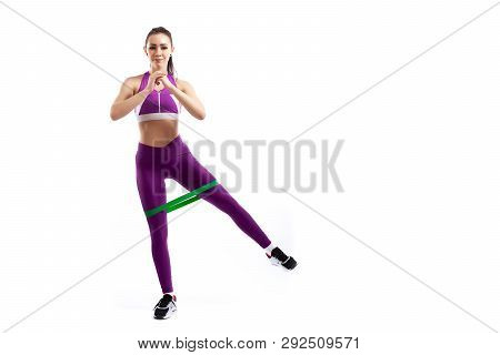 A Ypung Woman Coach In A Sporty Pink   Short Top And Gym Leggings Makes Lunges  By The Feet Forward