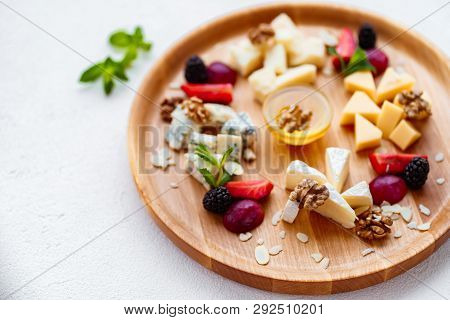 Assortment Of Different Cheese Types On Wooden Platter. Slices Of Cheese Camembert With Parmesan, Do