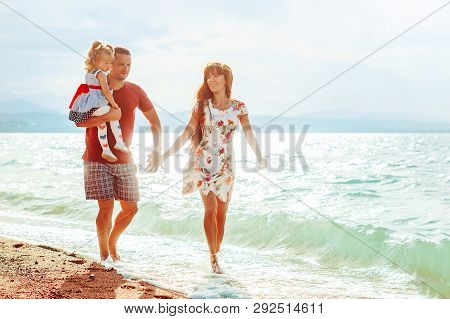 A Young Married Couple With A Child Walking On The Beach Near The Sea