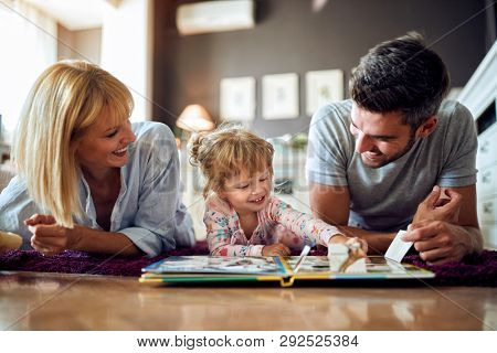 Cheerful mom and dad play with their kid in room