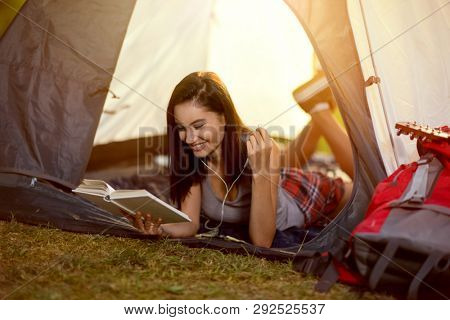 smiling girl reading a book in tent on camping