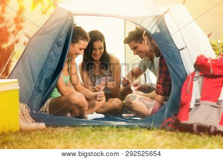 Group of young friends playing cards in tent on camping trip