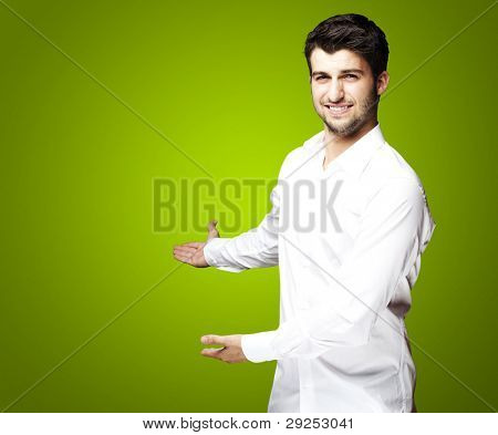 portrait of a handsome young man doing a welcome gesture over a green background