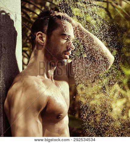 Muscular man taking shower outside
