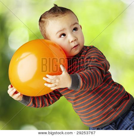 portrait of a funny kid holding a big orange balloon at the park
