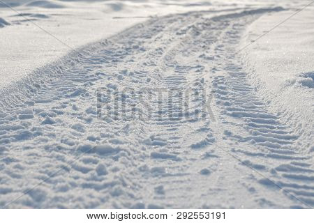 Car Tire Tracks On The Snow Closeup