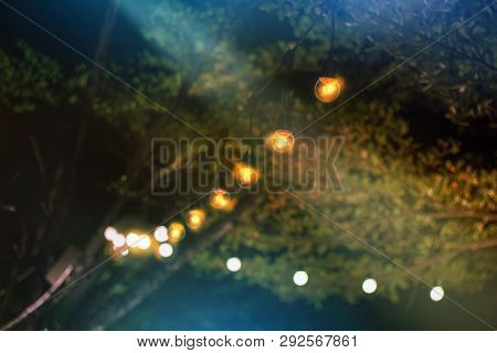 Yellow String Lights With Bokeh Decor At Backyard In Summer Night