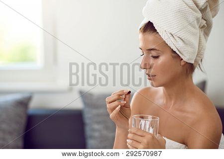 Attractive Young Woman With Her Hair And Body Wrapped In White Towels After Bathing Or Spa Treatment