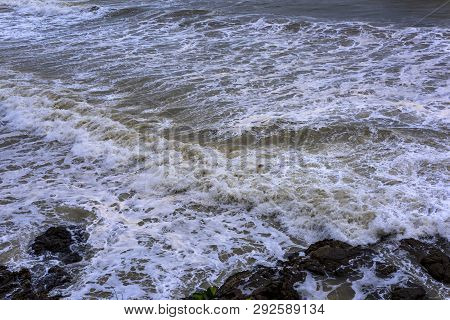 Sea waves breaking on a rocks. Deep blue sea waves hit cliff, hit rocks cliff. Mighty sea waves brea