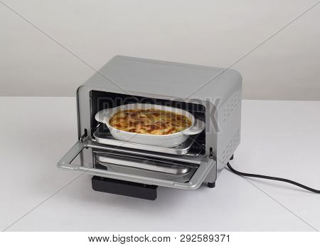 Opened Small Electric Oven With Tray Of Lasagna Inside, On White Background