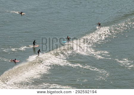 Sao Vicente, Brazil - July 2018:  A Group Of Paddleboarders Catch A Wave On A Warm Day Off The Coast