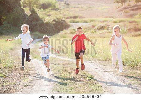 Four Little Kids Boys And Girls Running Fast Along Trail Outdoors Leisure Pursuit
