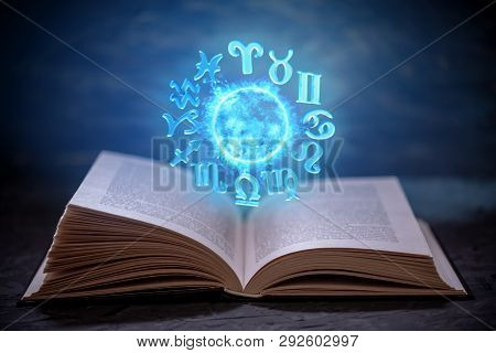Open Book On Astrology On A Dark Background. Glowing Magical Globe With Signs Of The Zodiac In The B