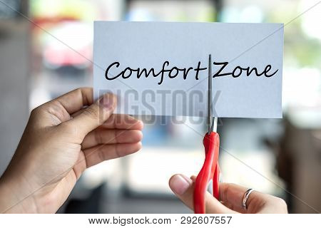 Business Man Hand Holding Red Scissors And Cutting White Paper With The Text Comfort Zone, Change Wo