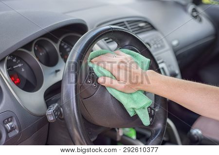 Young woman cleaning car interior with microfiber cloth. Car detailing. poster