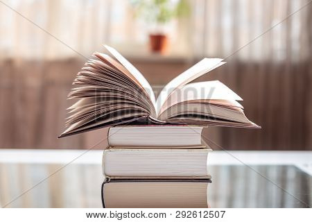 Open Book On A Stack Of Books On A Table In A Bright Room. Education And Reading Of Paper Books