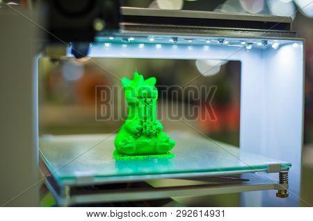 Print Head Of 3d Printer Machine Printing Plastic Model Of Green Toy Dragon At Modern Scifi Technolo
