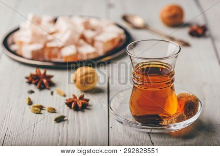 Asian tea in armudu glass with Rahat Lokum and different spices over wooden surface poster