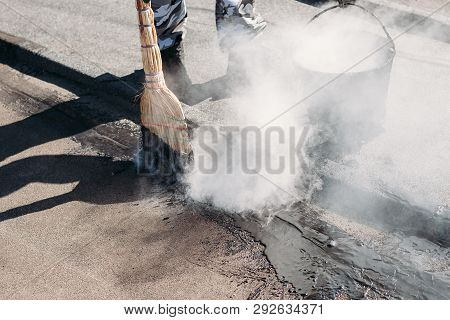 Worker repairs the roof with molten tar from a bucket with a broom. Roof repair tar. Poor repair of the roof tar poster