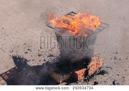 Molten hot tar in a bucket on the bricks. Roof repair. Fire from bucket. Grid on bucket poster