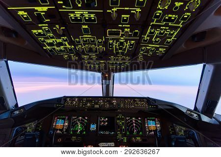Beautiful twilight sunset sky at high altitude from airplane cockpit view. Inside cockpit can see flight instruments of airplane. Seen from observer seat behind pilots. Modern aviation concept. poster