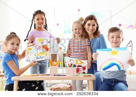 Cute Little Children With Teacher Showing Their Paintings At Lesson Indoors