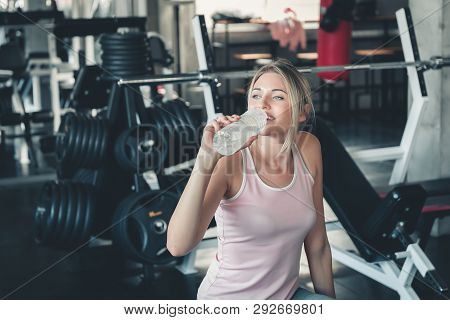 Beautiful Fitness Woman Is Drinking Water From Bottle After Working Out In Gym, Portrait Of Athletic