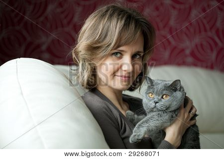 Pretty Young Woman Playing With A Gray Cat