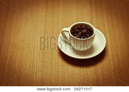 White Coffee Mug On White Plate Filled With Beans